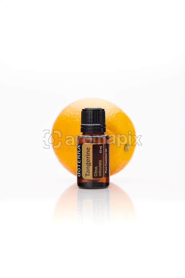 doTERRA Tangerine in front of a tangerine on a white background with reflection.