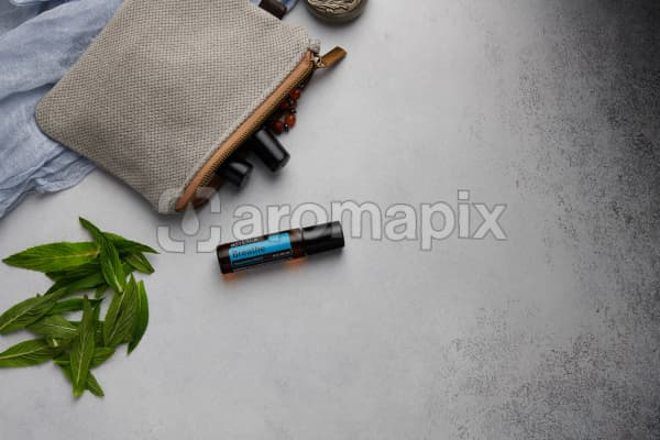 doTERRA Breathe Touch with clutch, accessories and mint leaves on a white concrete background.