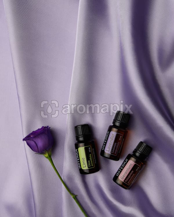 doTERRA Lime, Lavender and Geranium with a purple flower on pale purple satin.