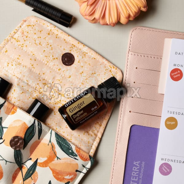 doTERRA Ginger on an essential oil bag with a flower, pen and diary on a white textured background.