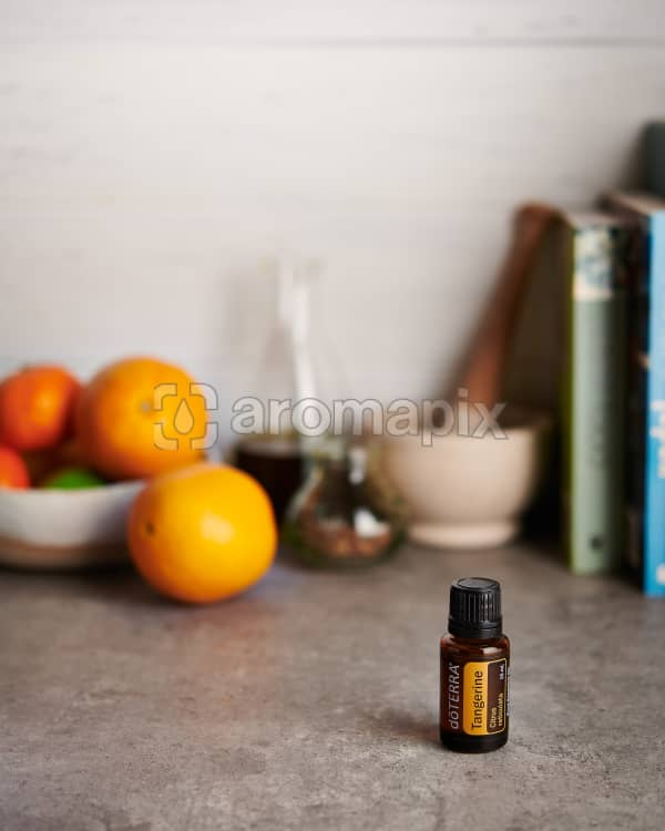 doTERRA Tangerine and a bowl of citrus fruit with kitchen equipment on a gray stone kitchen bench.