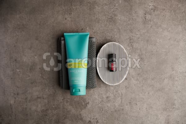 doTERRA Spa Hand and Body Lotion with Rose essential oil with bathroom accessories on a stone background.