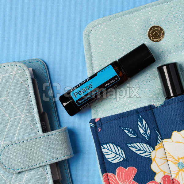 doTERRA Peace Touch on an essential oil bag with a diary on a blue textured background.