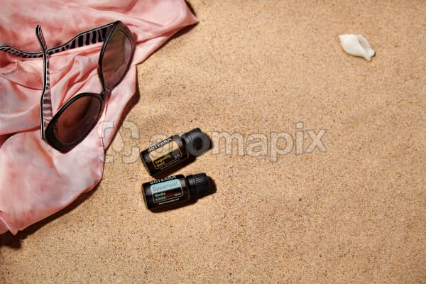 doTERRA Citrus Bliss and Spearmint with sunglasses and a pink silk scarf on the beach.