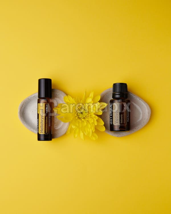 doTERRA Helichrysum Touch and Vetiver with a yellow flower on a yellow background.