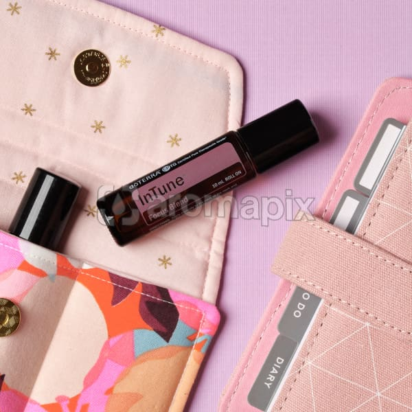 doTERRA InTune on an essential oil bag with a pink diary on a pale pink textured background.