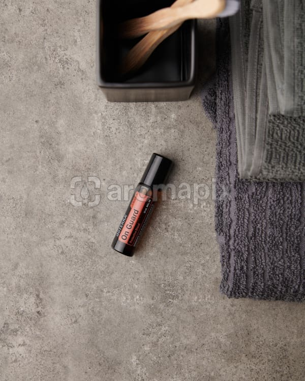 doTERRA On Guard Touch on a gray stone bathroom bench.