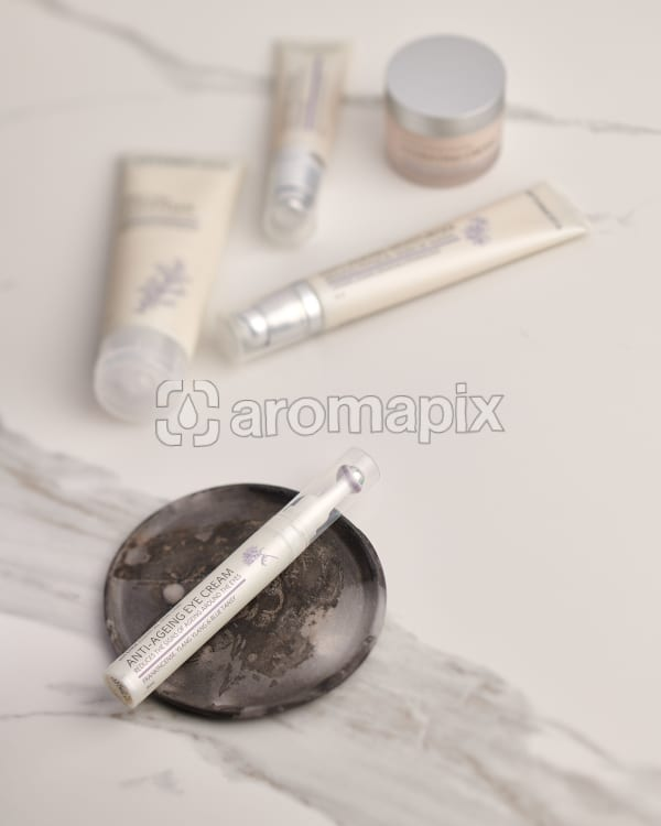 doTERRA Anti-Ageing Eye Cream on a ceramic plate with other Essential Skin Care products in the background on a white marble background.