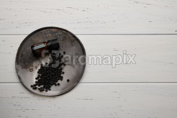 doTERRA Black Pepper and black peppercorns on a ceramic plate on a white wooden background.
