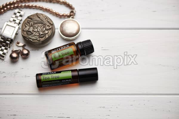 doTERRA Tea Tree oil and Tea Tree Touch, jewellery and trinkets on white rustic wooden background.
