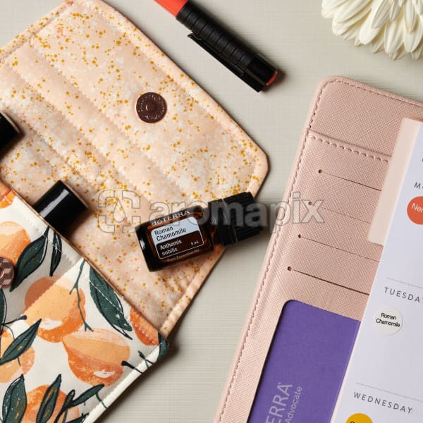 doTERRA Roman Chamomile on an essential oil bag with a white flower and diary on a white textured background.