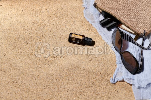 doTERRA Litsea with sunglasses, scarf and roller bottles in a clutch on the beach.