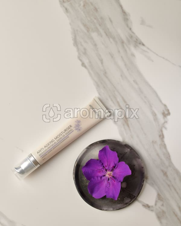 doTERRA Anti-Ageing Moisturiser with a purple flower in a gray ceramic plate on a white marble background.