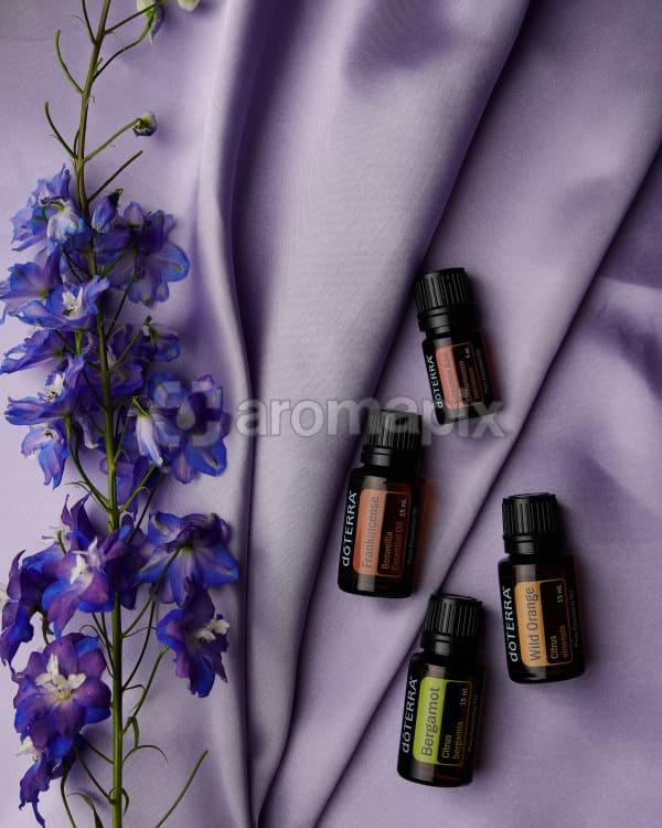 doTERRA Frankincense, Cinnamon Bark, Bergamot and Wild Orange with a purple flowers on pale purple satin.