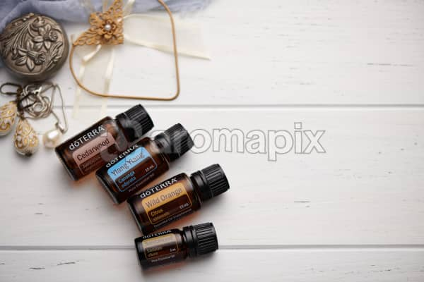 doTERRA Cedarwood, Ylang Ylang, Wild Orange and Sandalwood oils with romantic jewellery on a white vintage wooden background.