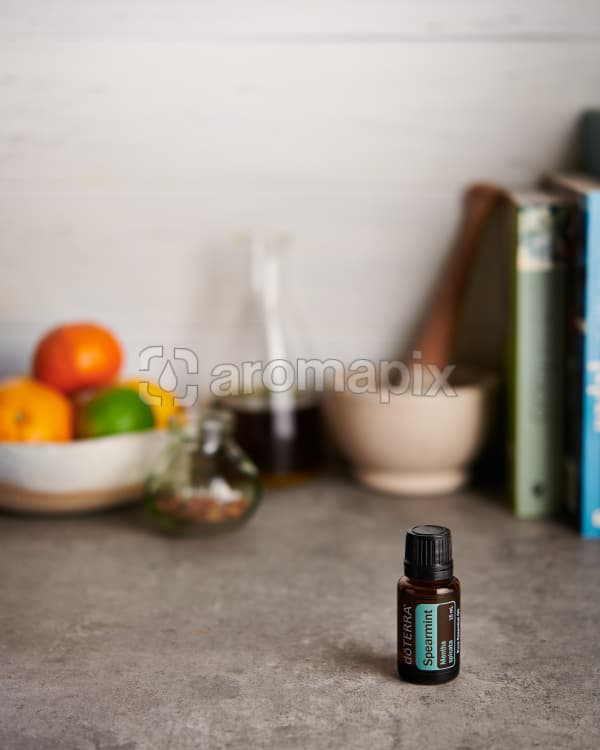 doTERRA Spearmint and a bowl of citrus fruit with kitchen equipment on a gray stone kitchen bench.