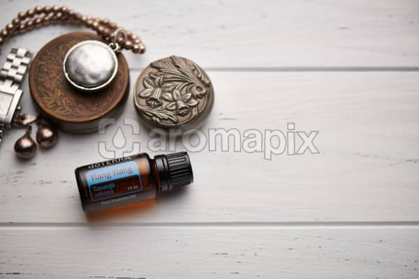 doTERRA Ylang Ylang, jewellery and trinkets on white rustic wooden background.