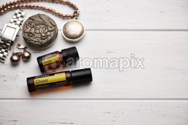 doTERRA Cheer oil and Cheer Touch blend, jewellery and trinkets on white rustic wooden background.