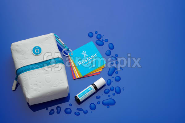 doTERRA Kids Oil Collection carry case, instructional flashcards and Rescuer 10ml Roll On on blue perspex with water.