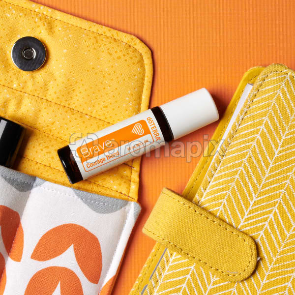 doTERRA Brave on an essential oil bag with a yellow diary on an orange textured background.