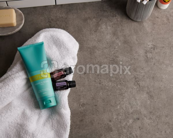 doTERRA Spa Hand and Body Lotion with Geranium and Patchouli essential oils and bathroom accessories on a white towel on a stone background.