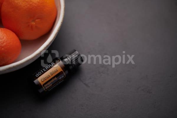 doTERRA RCitrus Bliss oil blend and citrus fruit in white ceramic bowl on black background.