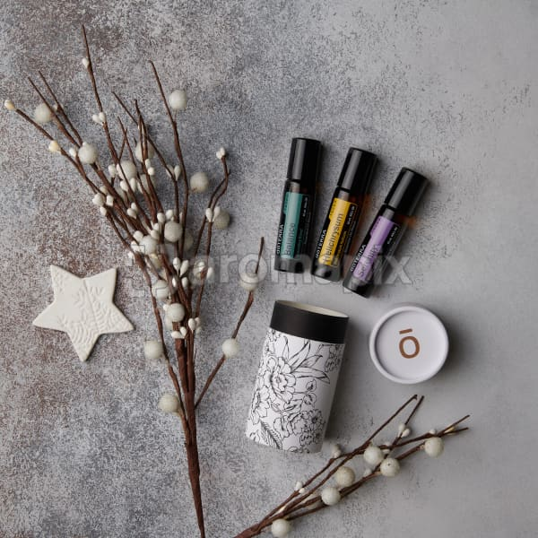doTERRA Balance Touch, Helichrysum Touch, and Serenity Touch with a beautiful cylinder gift box with holiday decorations on a speckled white background.
