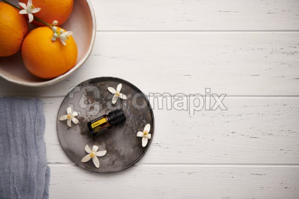 doTERRA Cheer with orange blossom flowers on a ceramic plate with a white ceramic bowl filled with seville oranges and orange blossoms on a white wooden background.