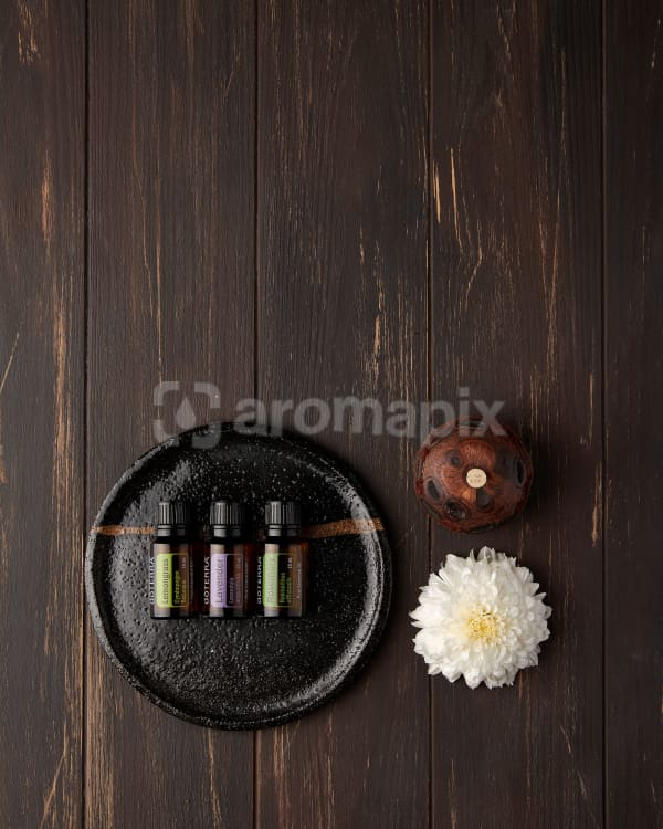 doTERRA Lemongrass, Lavender and Rosemary on a small ceramic plate with a flower and banksia seed pod diffuser on a brown wooden background.
