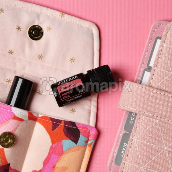 doTERRA Passion on an essential oil bag with a pink diary on a pink textured background.
