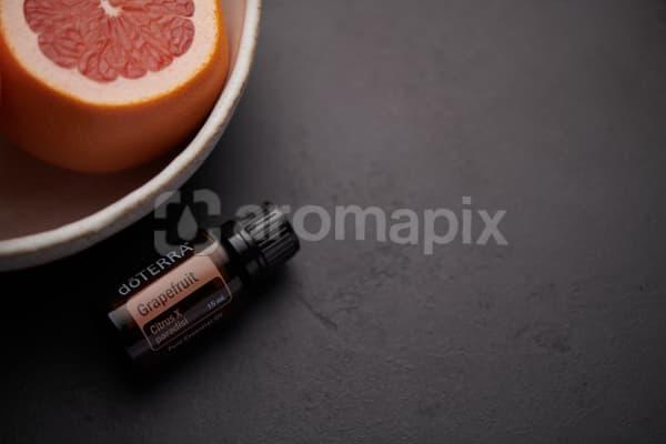 doTERRA Grapefruit oil and fruit in white ceramic bowl on black background.