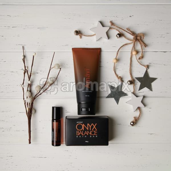 doTERRA Amavi Touch, Amavi After Shave Lotion and Onyx Balance Bath Bar with holiday decorations on a white wooden background.