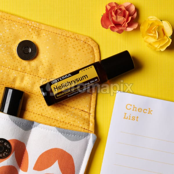 doTERRA Helichrysum Touch on an essential oil bag with scattered flowers and a check list on a yellow textured background.