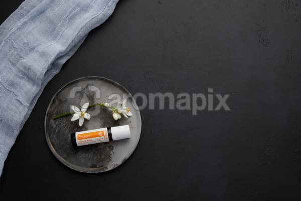 doTERRA Brave with orange blossom flowers on a ceramic plate on a black concrete baclground.