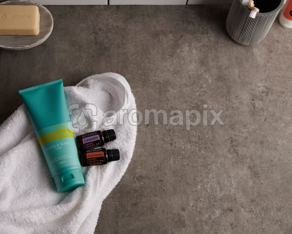doTERRA Spa Hand and Body Lotion with Lavender and Frankincense essential oils and bathroom accessories on a white towel on a stone background.