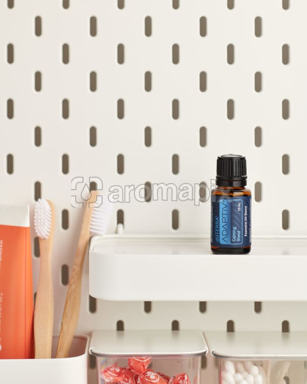 doTERRA Adaptive on a bathroom shelf with additional doTERRA products and bathroom accessories.