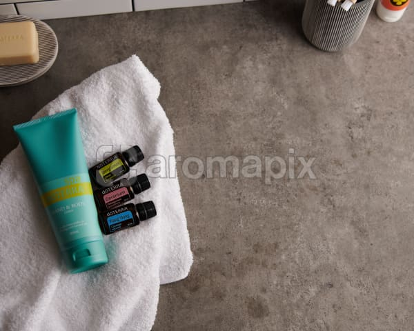 doTERRA Spa Hand and Body Lotion with Bergamot, Geranium and Ylang Ylang essential oils and bathroom accessories on a white towel on a stone background.
