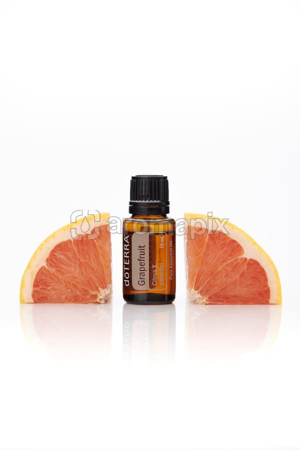 doTERRA Grapefruit with grapefruit pieces on a white background with reflection.