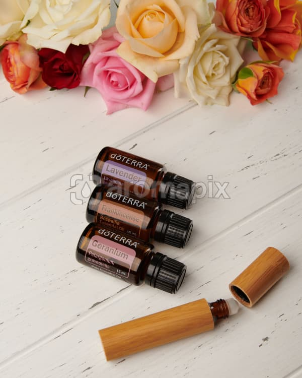 doTERRA Lavender, Frankincense and Geranium with a bamboo roller bottle and roses on a white wooden background.
