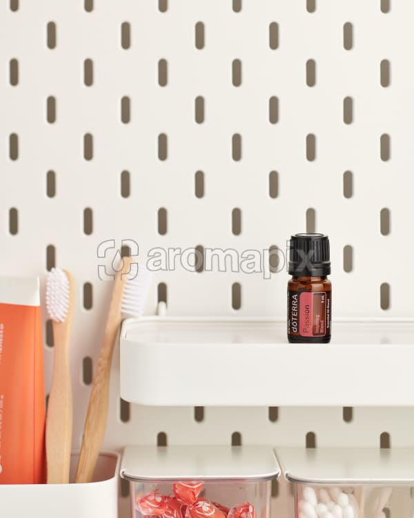 doTERRA Passion Inspiring Blend on a bathroom shelf with additional doTERRA products and bathroom accessories.