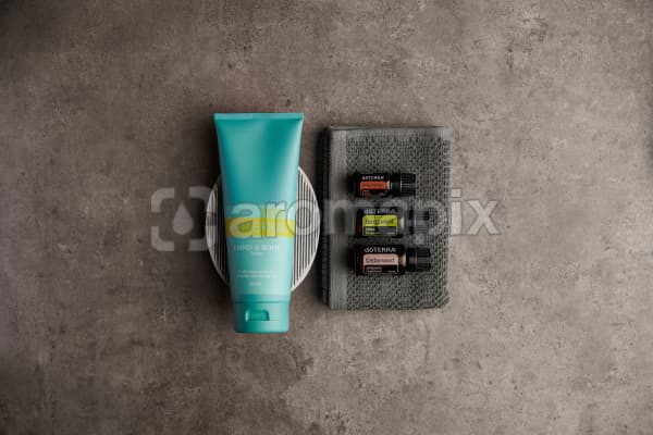 doTERRA Spa Hand and Body Lotion with Arborvitae, Bergamot and Cedarwood essential oils with bathroom accessories on a stone background.