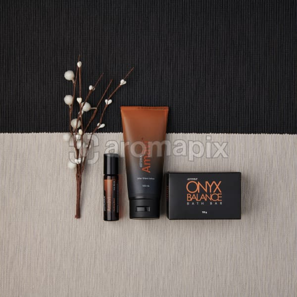 doTERRA Amavi Touch, Amavi After Shave Lotion and Onyx Balance Bath Bar with a holiday decoration on a dark and light gray textured backround.