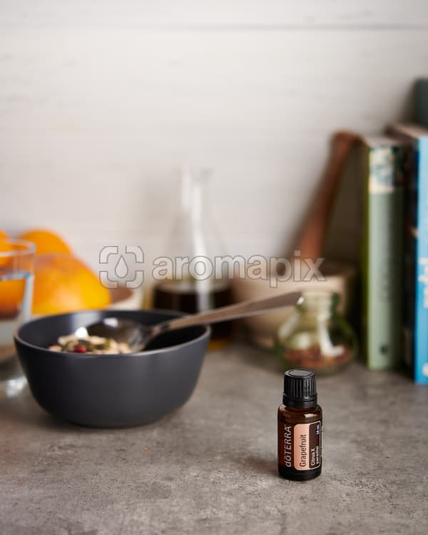 doTERRA Grapefruit with kitchen items on a gray stone kitchen bench.