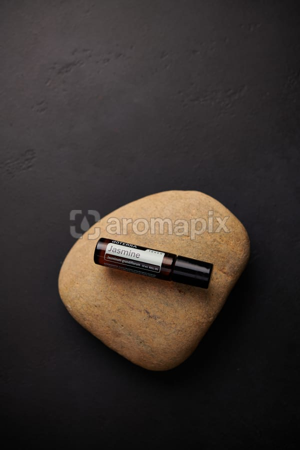 doTERRA Jasmine Touch sitting on a stone on a black concrete background.
