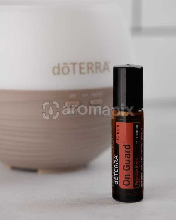 doTERRA On Guard Touch and a doTERRA Petal Diffuser 2.0 on a pale gray background.