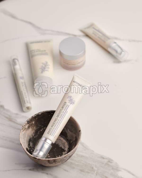 doTERRA Anti-Ageing Moisturiser in a ceramic bowl with other Essential Skin Care products in the background on a white marble background.