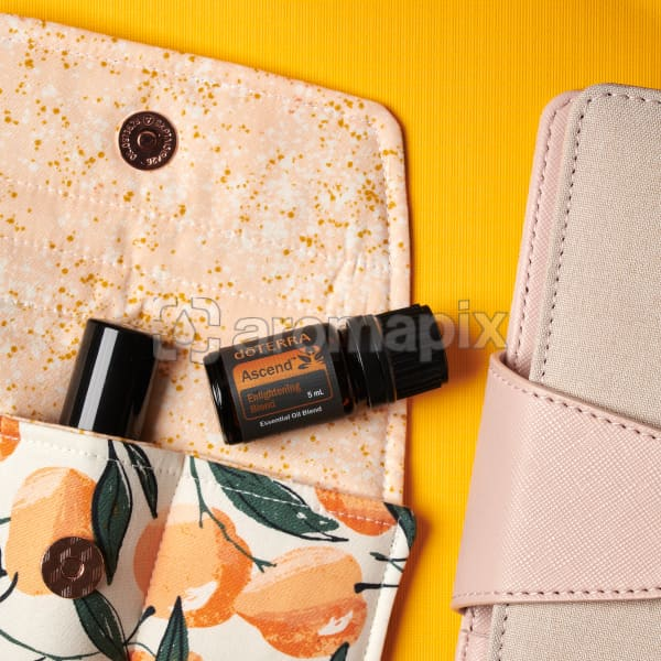 doTERRA Ascend on an essential oil bag with a pink diary on a yellow textured background.