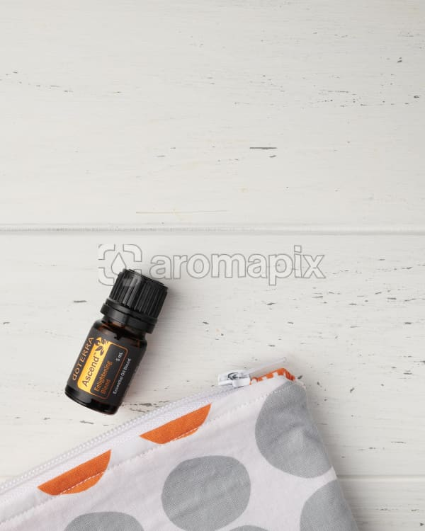 doTERRA Ascend and an essential oil bag on a white wooden background.