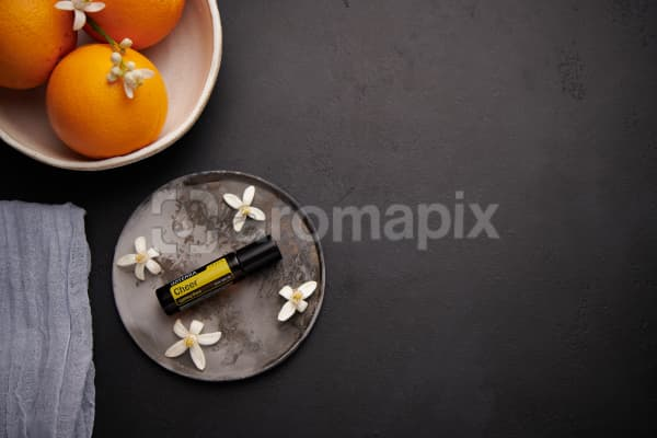 doTERRA Cheer Touch with orange blossom flowers on a ceramic plate with a white ceramic bowl filled with seville oranges and orange blossoms on a black concrete background.