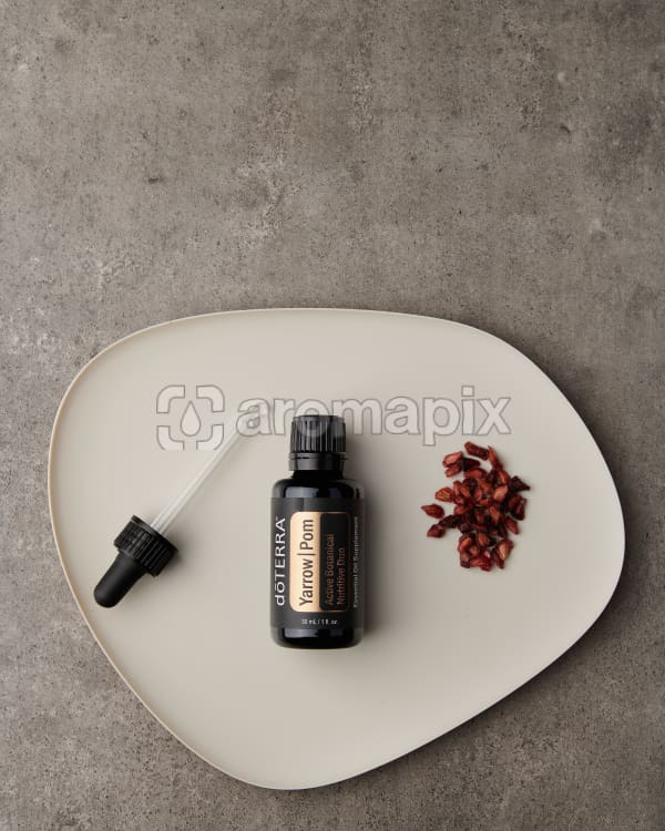 doTERRA Yarrow Pom with pomegranate seeds on a white plate on a gray stone background.